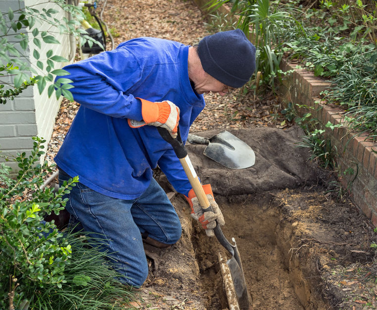 Man digging trench to replace old sewer pipes and lawn sprinkler system line