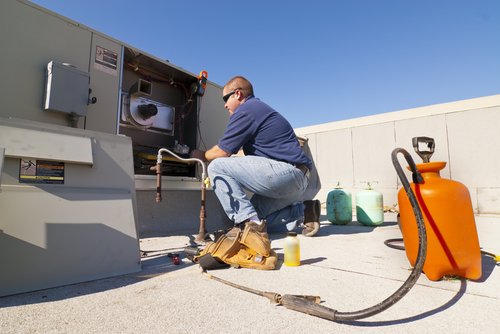 Technician repairing HVAC unit